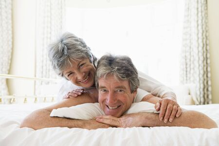 Couple lying on bed together smiling photo