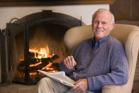 Man sitting in living room by fireplace with newspaper smiling Stock Photo - 3475947
