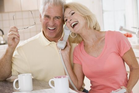 Couple in kitchen using telephone together and laughing photo
