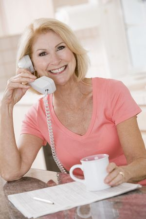 Woman in kitchen using telephone and smiling photo