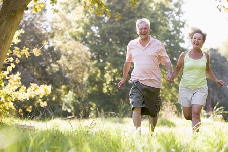 Couple running in park holding hands and smiling photo