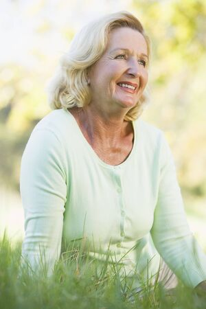Woman sitting outdoors smiling Stock Photo - 3475660