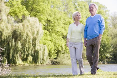 fit: Couple walking outdoors at park by lake smiling