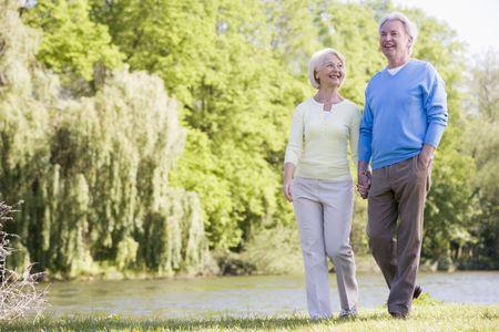 ancianos caminando: Pareja caminando al aire libre en el parque de lago sonriente