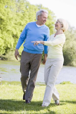 Couple walking outdoors at park by lake smiling photo