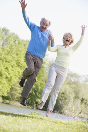 fits in: Couple jumping outdoors at park by lake smiling