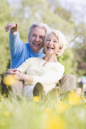 Couple relaxing outdoors pointing and smiling photo