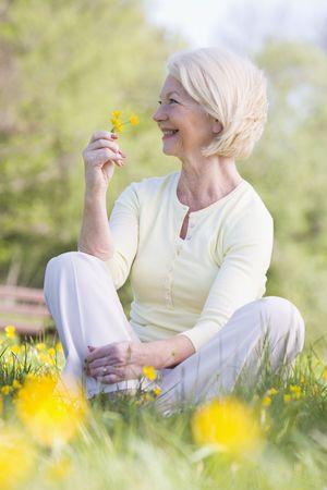 buttercup flower: Woman sitting outdoors smiling and holding a Buttercup flower