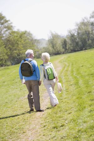 Couple walking on path in park holding hands photo