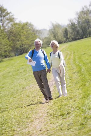 Couple walking on path in park holding hands and smiling Stock Photo - 3475911