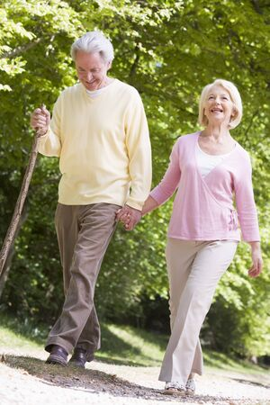 Couple walking on path in park holding hands and smiling photo