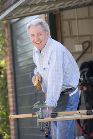 sawing: Man at shed sawing wood and smiling