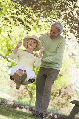 Couple outdoors with tree swing smiling Stock Photo - 3475820