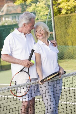 playing tennis: Couple playing tennis and smiling