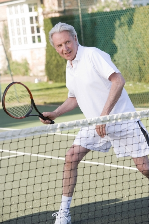 Man playing tennis and smiling photo