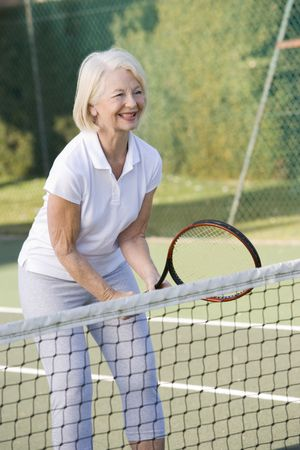playing tennis: Woman playing tennis and smiling