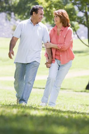 Couple holding hands outdoors by lake smiling photo