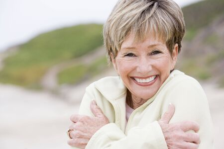 cosy: Woman at the beach cold and smiling Stock Photo