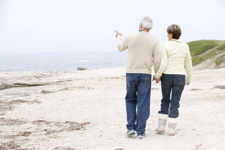 Couple at the beach holding hands and pointing photo