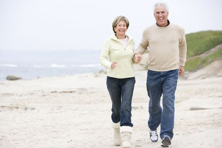 Couple at the beach holding hands and smiling Stock Photo - 3475626
