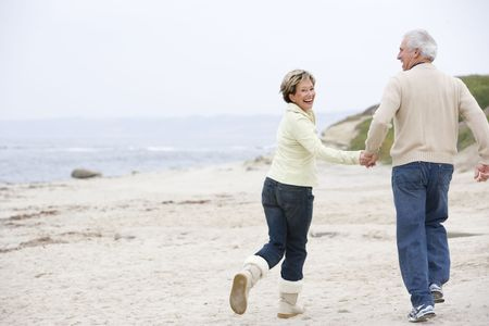 retired: Couple at the beach holding hands and smiling