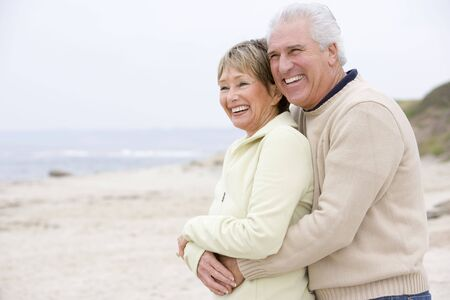 Couple at the beach embracing and smiling photo