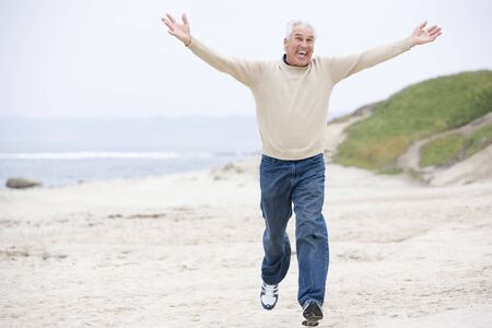 energetic people: Man at the beach running and smiling Stock Photo