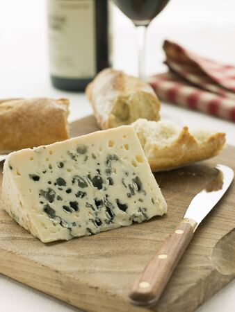 Wedge of Roquefort Cheese with Rustic Baguette and Red Wine photo