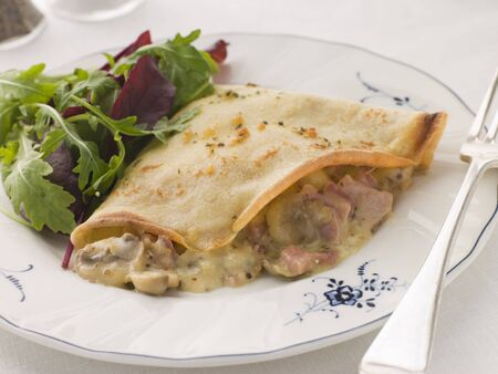 crepe: Savoury Pancake filled with Ham Cheese and Mushrooms with dressed salad Stock Photo