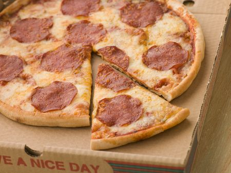 Pepperoni Pizza in a Take Away Box with a Cut Slice photo