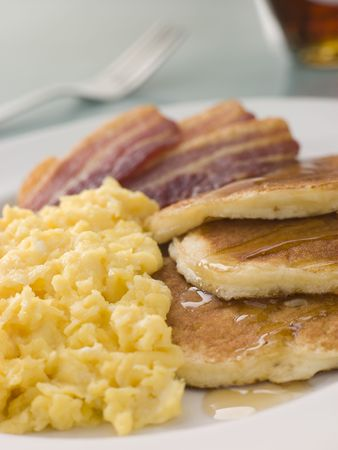 scrambled: American Pancakes with Crispy Bacon and Scrambled Eggs and Maple Syrup Stock Photo