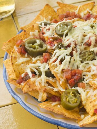 Platter of Nachos with Salsa Jalapenos and Cheese photo