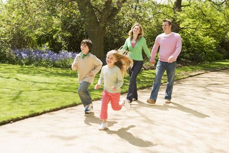 park path: Family running on path holding hands smiling