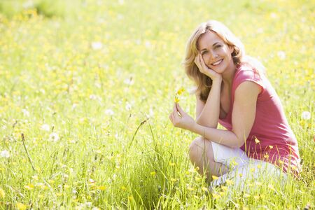 crouching: Woman outdoors holding flower smiling