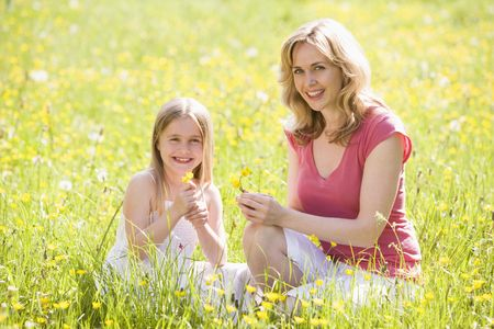 Mother and daughter outdoors holding flower smiling Stock Photo - 3476260
