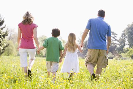 children walking: Family walking outdoors holding hands Stock Photo
