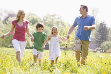 笑みを浮かべて歩いて屋外を保持している家族を手します。 写真素材