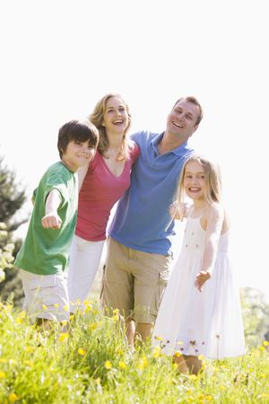 male age 40's: Family standing outdoors holding hands smiling