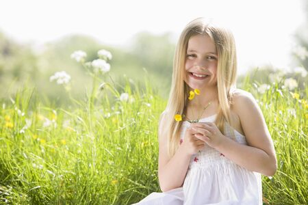Young girl sitting outdoors holding flower smiling photo