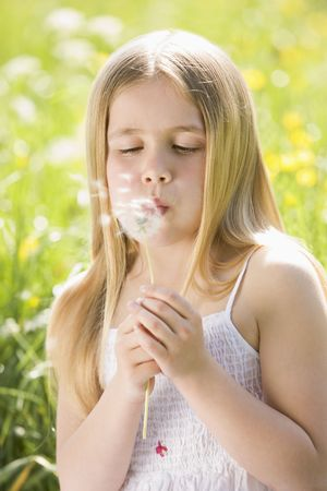 Young girl sitting outdoors blowing dandelion head photo