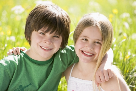 Two young children sitting outdoors arm in arm smiling photo