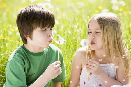 Two young children sitting outdoors blowing dandelion heads smiling