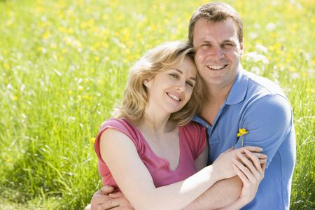 countryside loving: Couple sitting outdoors holding flower smiling Stock Photo
