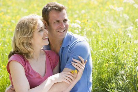 Couple sitting outdoors holding flower smiling photo