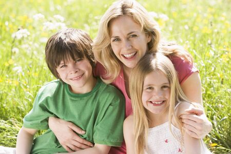 young boy smiling: Mother and two young children sitting outdoors smiling