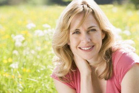 Frau sitzt im Freien lächeln Standard-Bild