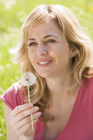 Woman sitting outdoors holding dandelion head smiling photo