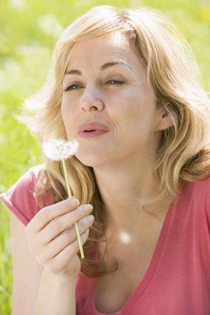 generation x: Woman sitting outdoors blowing dandelion head Stock Photo