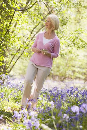bluebell woods: Woman walking outdoors holding flower smiling Stock Photo