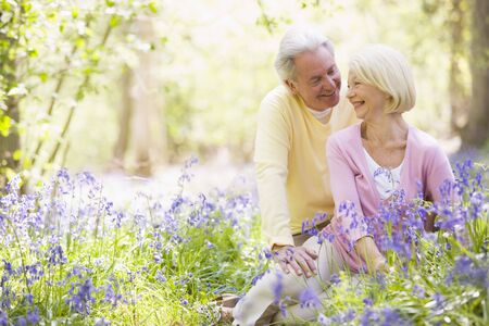 bluebell woods: Couple sitting outdoors with flowers smiling